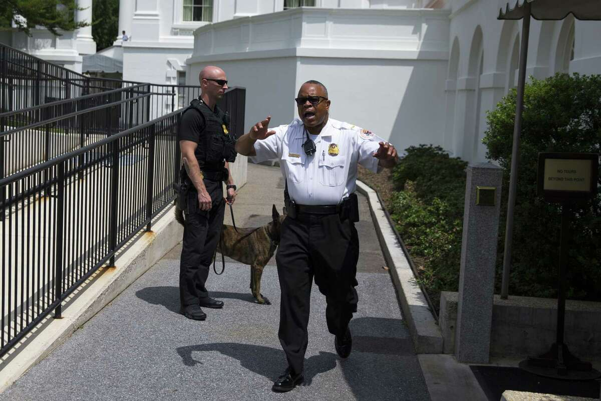 Secret Service police move members of the media outside the briefing room as they evacuate parts of the White House in Washington, Tuesday, June 9, 2015.