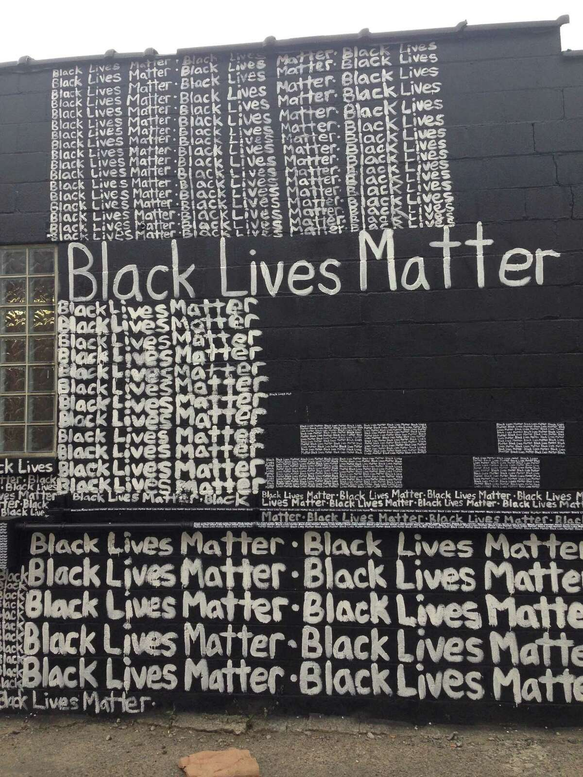 """""""Black Lives Matter"""" is painted repeatedly on the exterior wall behind the N'Namdi Center for Contemporary Art in Detroit."""