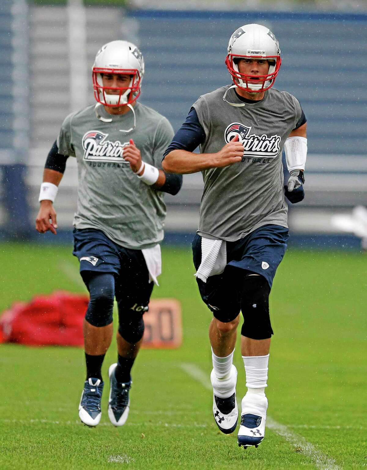 Patriots quarterback Tom Brady, right, and quarterback Jimmy Garoppolo work out during an organized team activity last Thursday.