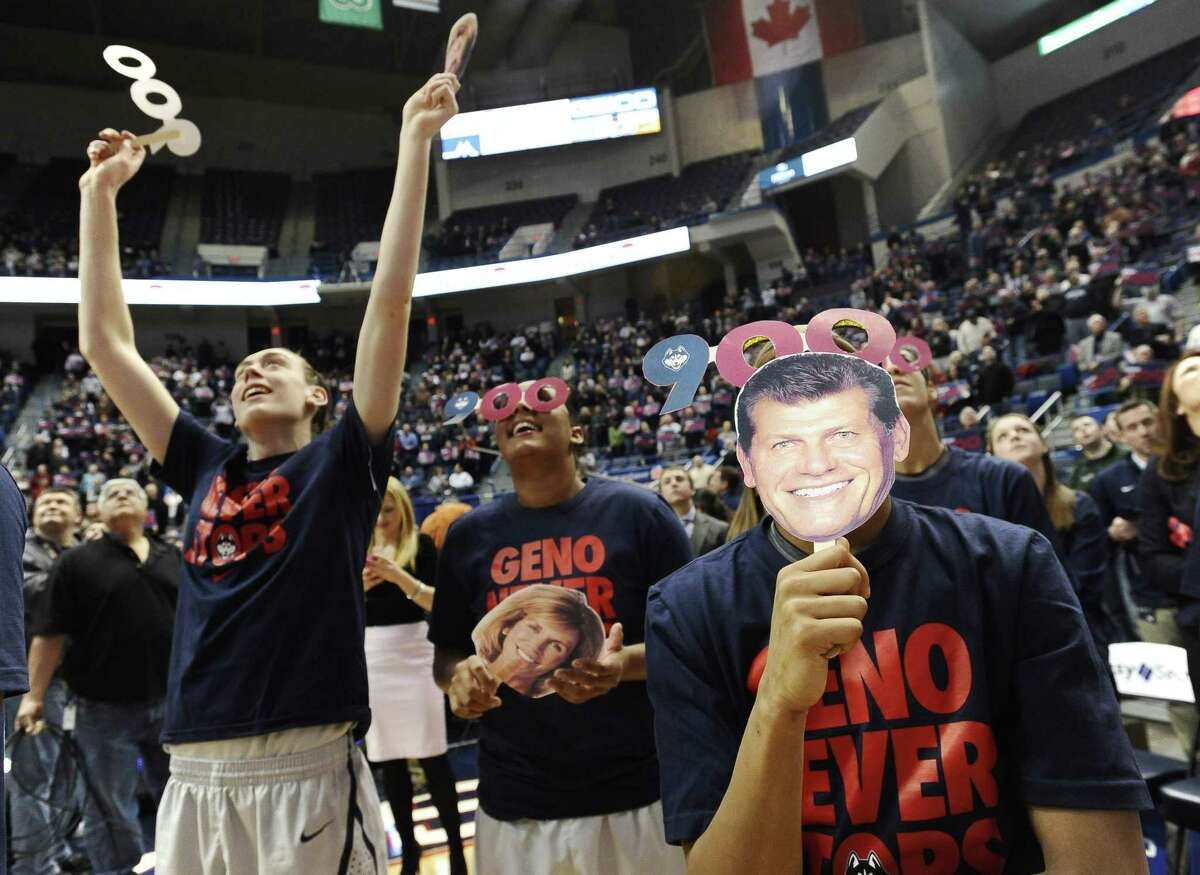 UConn's Moriah Jefferson, right, holds up a mask with the likeness of coach Geno Auriemma as teammates Breanna Stewart, left, and Kaleena Mosqueda-Lewis watch a video tribute after the Hall of Famer's 900th career win on Tuesday in Hartford.