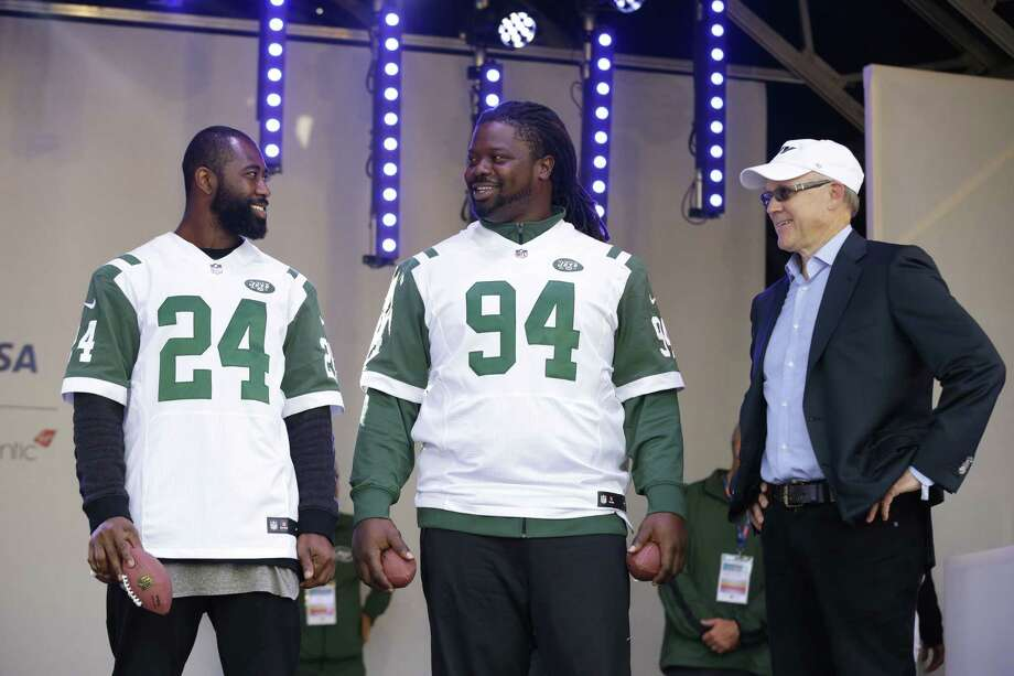 New York Jets owner Woody Johnson, right, cornerback Darrelle Revis, left, and nose tackle Damon Harrison stand on stage during an NFL fan rally in Trafalgar Square, in London on Saturday. Photo: The Associated Press  / AP