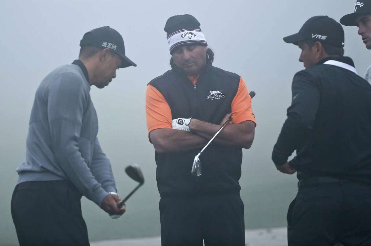 Tiger Woods works on his short game technique as fellow PGA Tour player Pat Perez, center, and coach Chris Como look on during a fog delay prior to the pro-am at the Farmers Insurance Open Wednesday at Torrey Pines in San Diego.