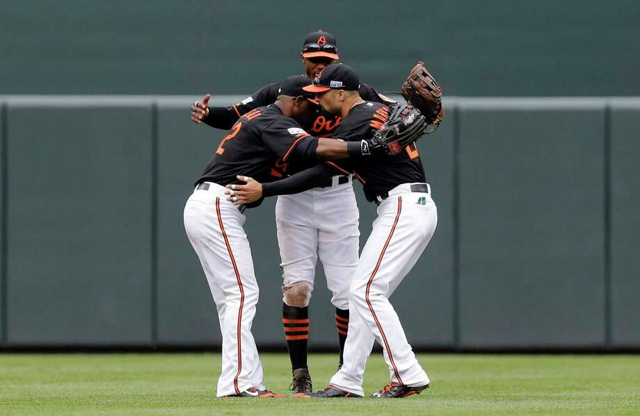 From left, Orioles outfielders Alejandro De Aza, Adam Jones and Nick Markakis celebrate after Game 2 of the American League Division Series against the Detroit Tigers on Friday in Baltimore. Photo: Patrick Semansky — The Associated Press  / AP