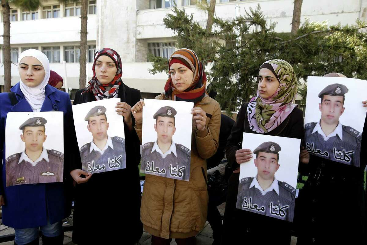 """Anwar al-Tarawneh, center, the wife of Jordanian pilot, Lt. Muath al-Kaseasbeh, who is held by Islamic State group militants, holds a poster of him with Arabic that reads, """"we are all Muath,"""" during a protest in Amman, Jordan, Tuesday, Feb. 3, 2015. An online video released Tuesday, Feb. 3, 2015 purportedly shows a Jordanian pilot captured by the Islamic State extremist group being burned to death. The Associated Press was not immediately able to confirm the authenticity of the video, which was released on militant websites and bore the logo of the extremist group's al-Furqan media service."""
