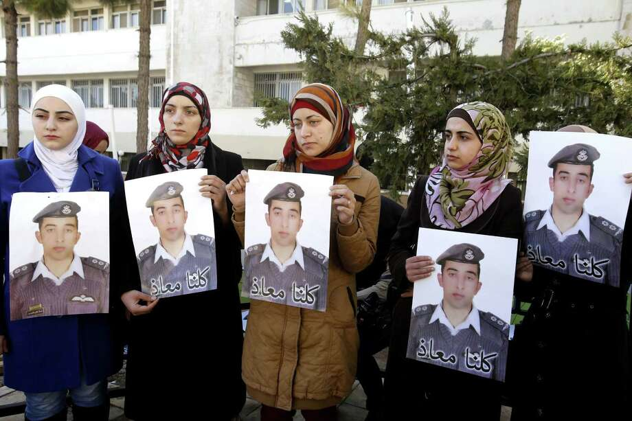 "Anwar al-Tarawneh, center, the wife of Jordanian pilot, Lt. Muath al-Kaseasbeh, who is held by Islamic State group militants, holds a poster of him with Arabic that reads, ""we are all Muath,"" during a protest in Amman, Jordan, Tuesday, Feb. 3, 2015. An online video released Tuesday, Feb. 3, 2015 purportedly shows a Jordanian pilot captured by the Islamic State extremist group being burned to death. The Associated Press was not immediately able to confirm the authenticity of the video, which was released on militant websites and bore the logo of the extremist group's al-Furqan media service. Photo: (AP Photo/Raad Adayleh) / AP"