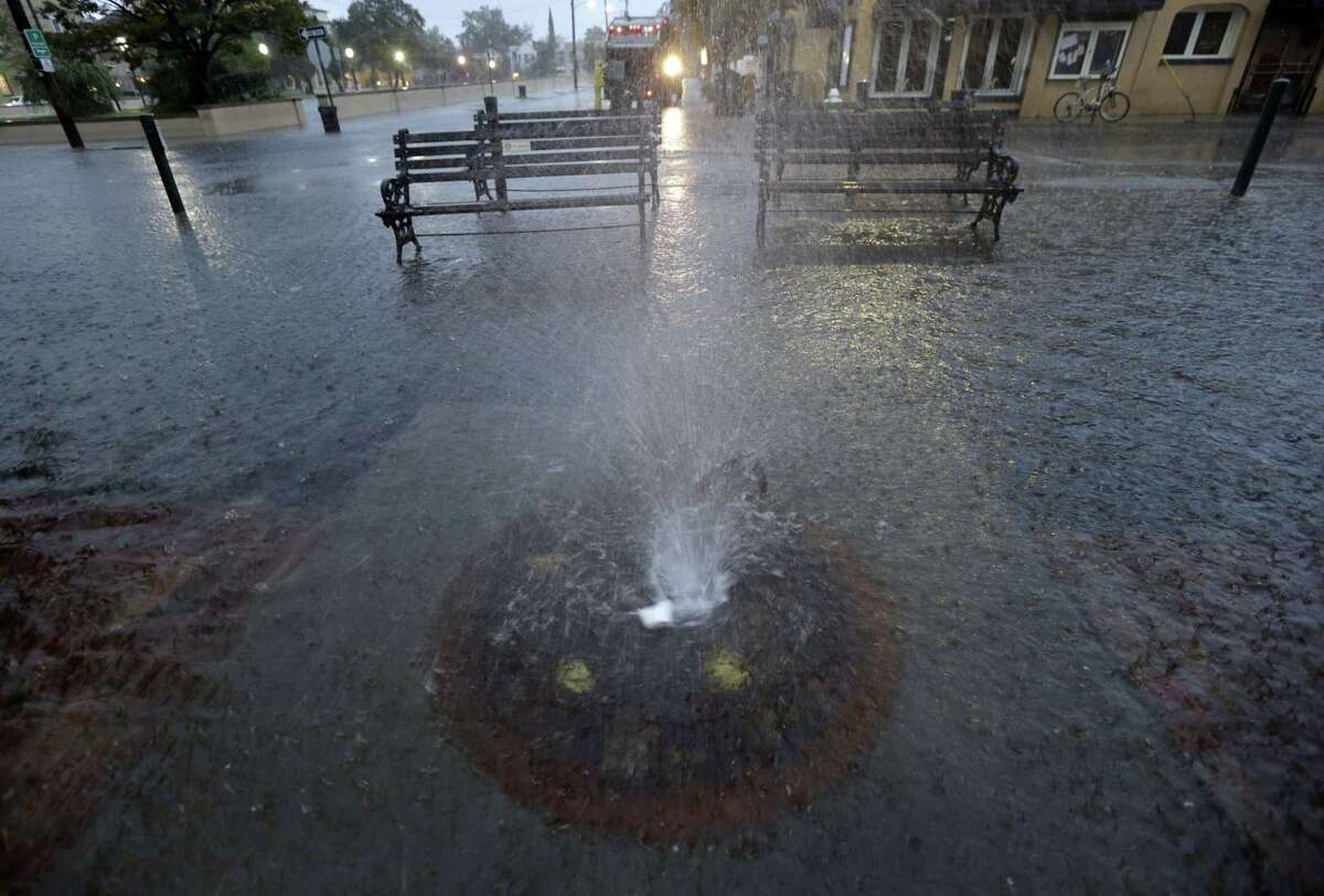 Storm waters squirts from a storm drain in downtown Charleston, S.C., Saturday, Oct. 3, 2015. The National Weather Service says the risk of flooding will continue through Monday morning, especially in parts of North and South Carolina that already have gotten up to 11 inches of rain this week. Forecasters say some areas could see storm totals as high as 15 inches.
