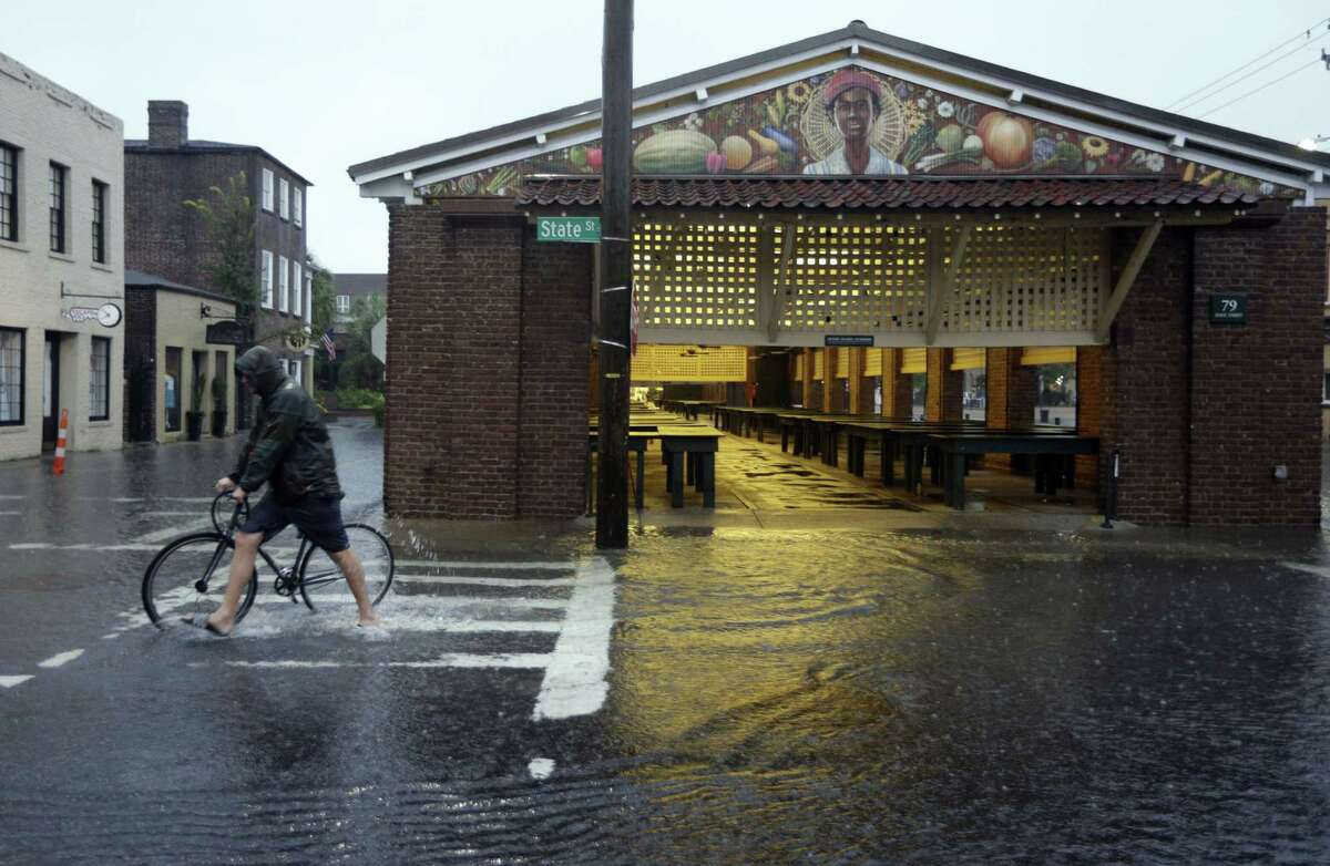 A man walks his bicycle through high water at the City Market in downtown Charleston, S.C., Saturday, Oct. 3, 2015. The National Weather Service says the risk of flooding will continue through Monday morning, especially in parts of North and South Carolina that already have gotten up to 11 inches of rain this week. Forecasters say some areas could see storm totals as high as 15 inches.