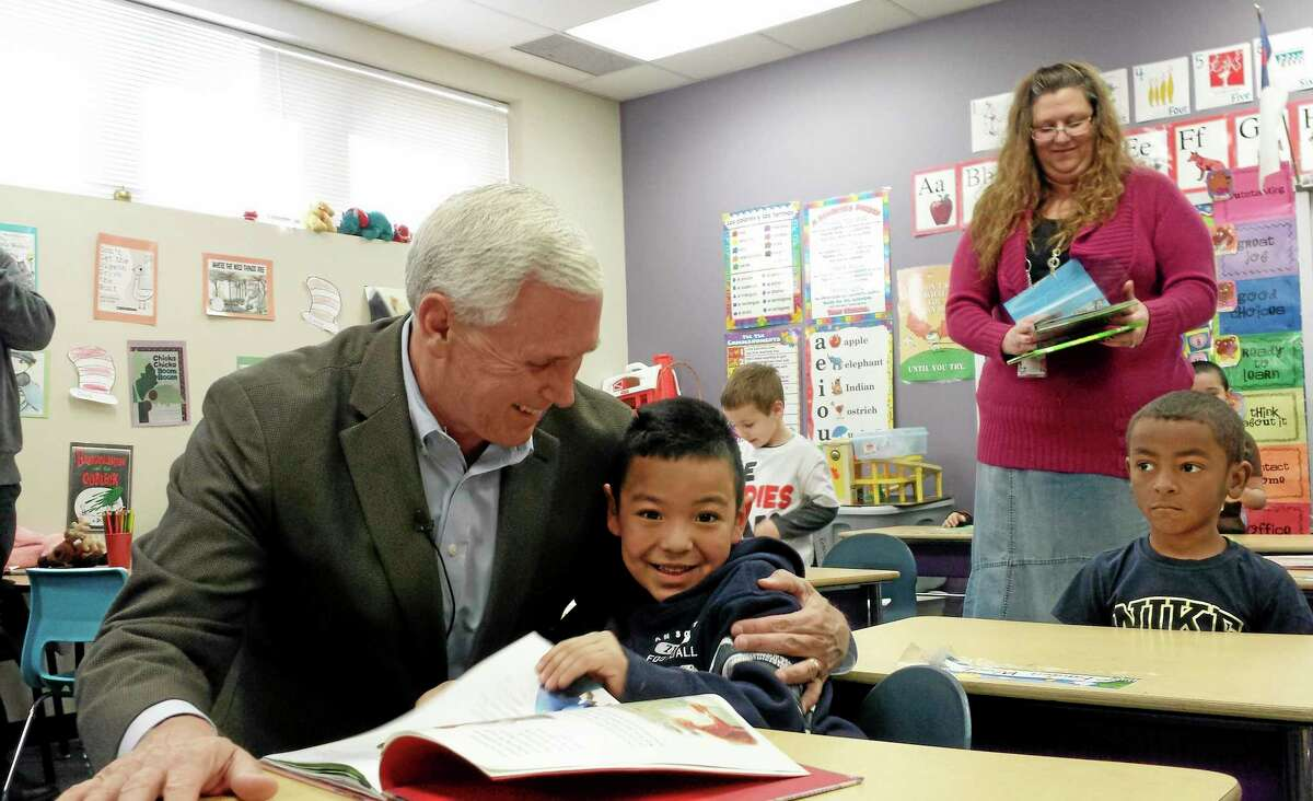 FILE - In this Feb. 26, 2014 file photo Indiana Republican Gov. Mike Pence embraces a preschool student at the Shepherd Community Center in Indianapolis. Pence's office says he signed a bill said Monday, March 24, 2014 pulling Indiana from reading and math standards that were adopted by most states around the country. (AP Photo/Tom LoBianco, File)