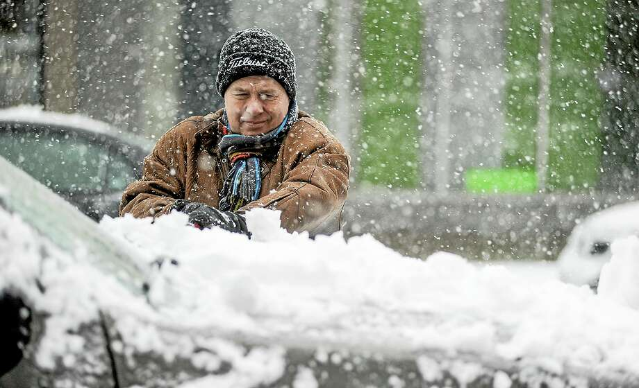 Curt Anderson clears snow from his vehicle in downtown Austin, Minn., Thursday. Photo: The Associated Press — Austin Daily Herald, Eric Johnson  / Austin Daily Herald