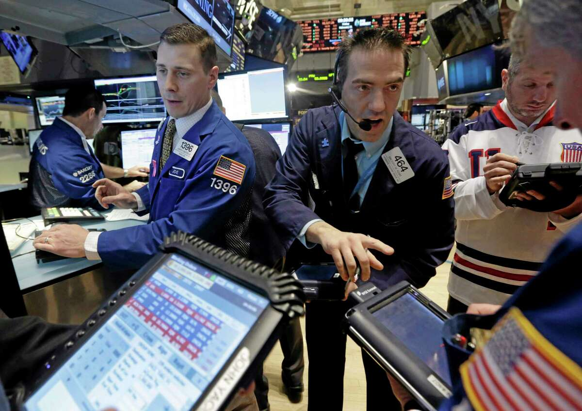 Trader Gregory Rowe, center, works at the post of specialist Joseph Mastrolia, left, on the floor of the New York Stock Exchange Friday.