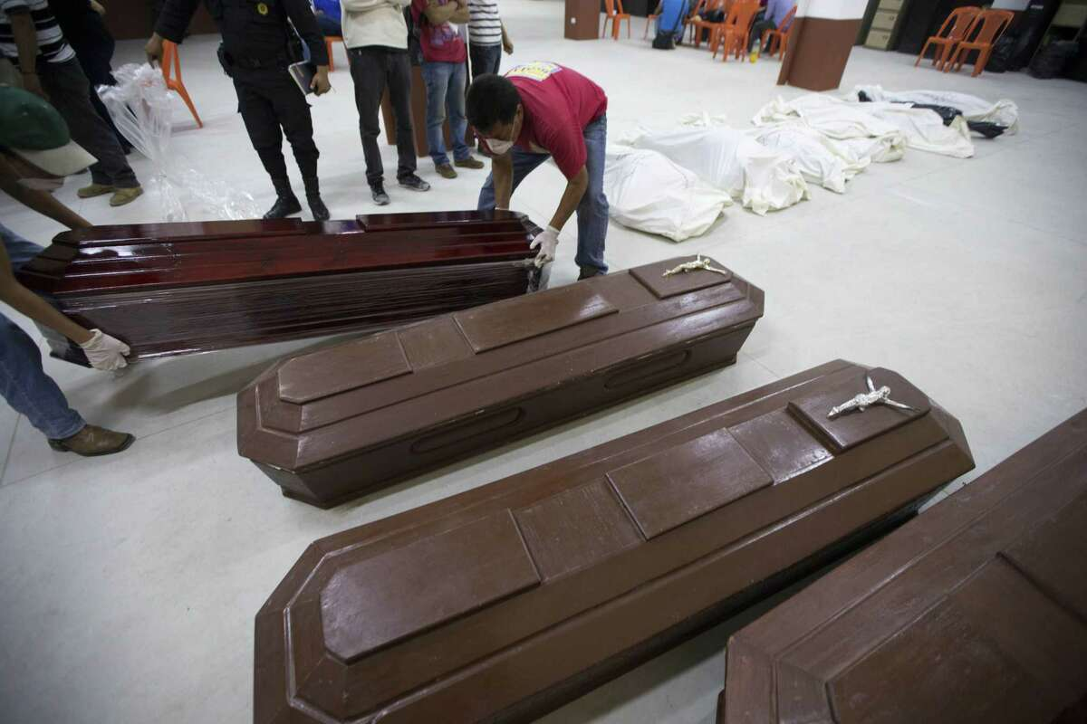 Volunteers arrange coffins at a provisional morgue in Santa Catarina Pinula, Guatemala, Friday, Oct. 2, 2015. The hill that towers over the Santa Catarina Pinula neighborhood known as Cambray, collapsed late Thursday after heavy rains, burying several houses with dirt, mud and rocks. Family members have reported 100 people missing, but the number could be as high as 600 based on at least 100 homes in the area of the slide, said Alejandro Maldonado, executive secretary of Conred, the country's emergency disaster agency.