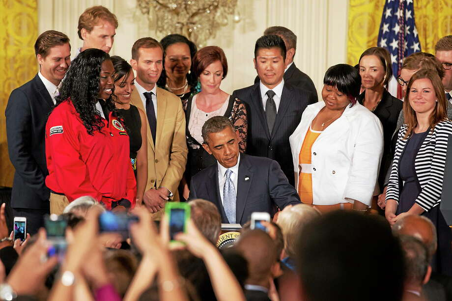 Surrounded by college students, President Barack Obama signs a Presidential Memorandum on reducing the burden of student loan debt on June 9, 2014, in the East Room of the White House. Photo: AP Photo/Jacquelyn Martin  / AP