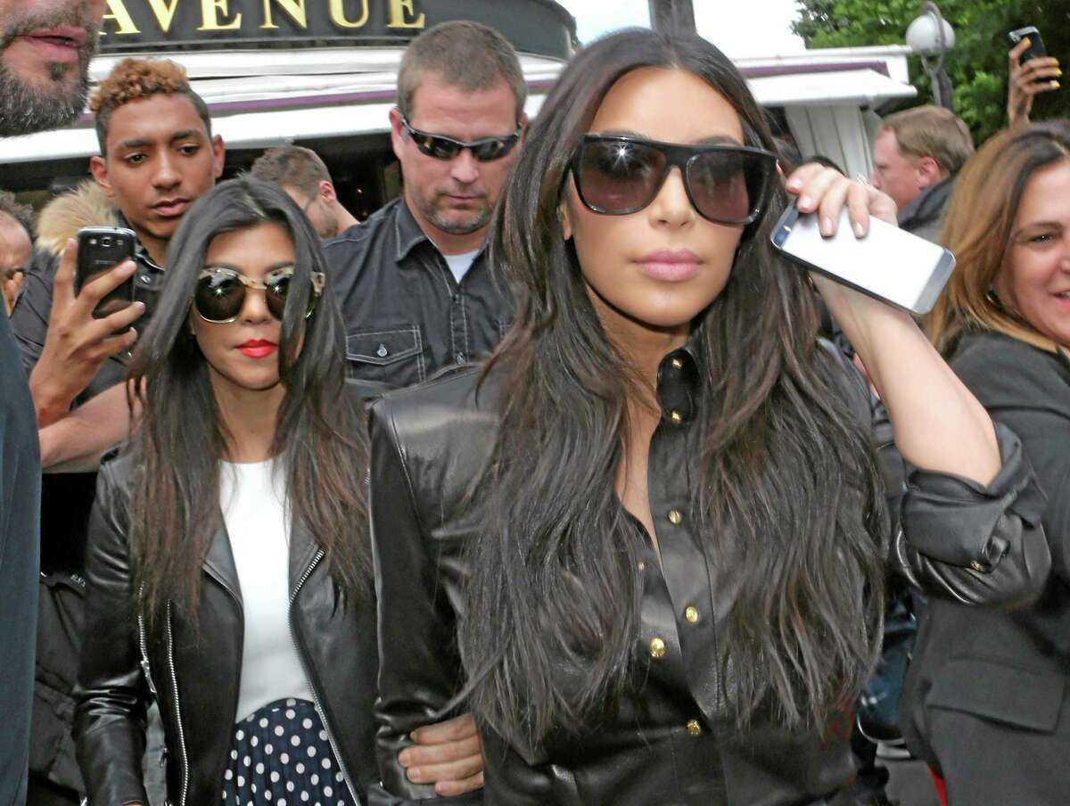 Kim Kardashian, front and Kourtney Kardashian, left, leave at a restaurant in Paris, Thursday, May 22, 2014.