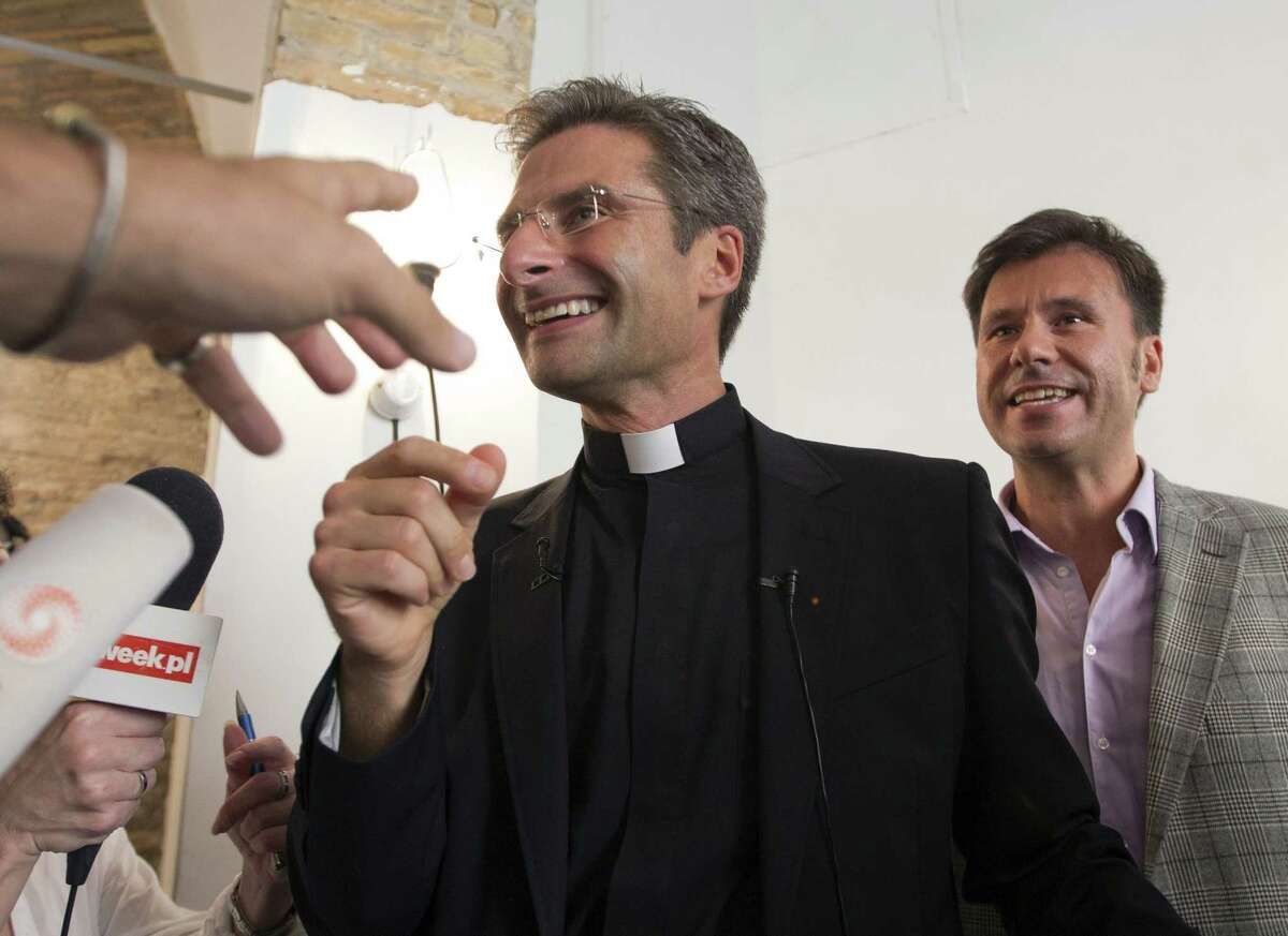 Monsignor Krzysztof Charamsa, left, and his partner Eduard, surname not given, leave a restaurant in downtown Rome, Saturday Oct. 3, 2015. The Vatican on Saturday fired Charamsa who came out as gay on the eve of a big meeting of the world's bishops to discuss church outreach to gays, divorcees and more traditional Catholic families.