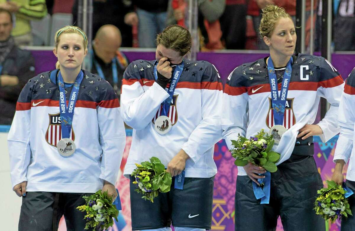 United States women's hockey players, from left, Monique Lamoureux, Megan Bozek and Meghan Duggan, react after losing 3-2 in overtime to Canada in the gold-medal game Thursday at Winter Olympics in Sochi, Russia.