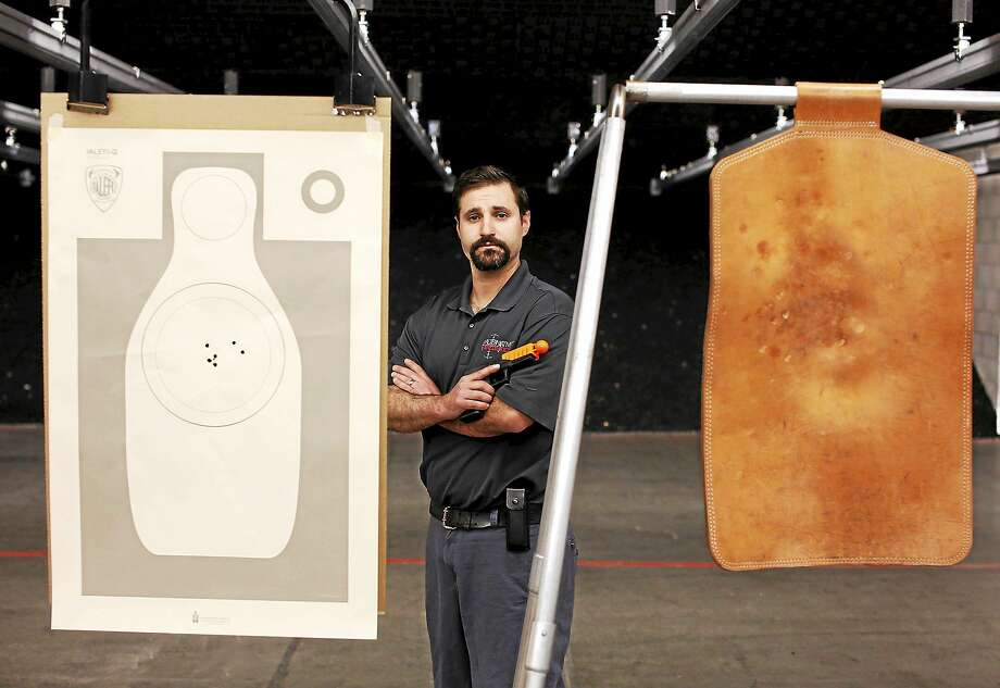 "Alternative Ballistics chief executive Christian Ellis stands next to a target, right, at which he fired the Alernative, which attaches to a handgun and creates a ""less-lethal"" round. Standard bullets were fired at the other target. Photo: Earnie Grafton/for The Washington Post  / Copyright 2015 Earnie Grafton"