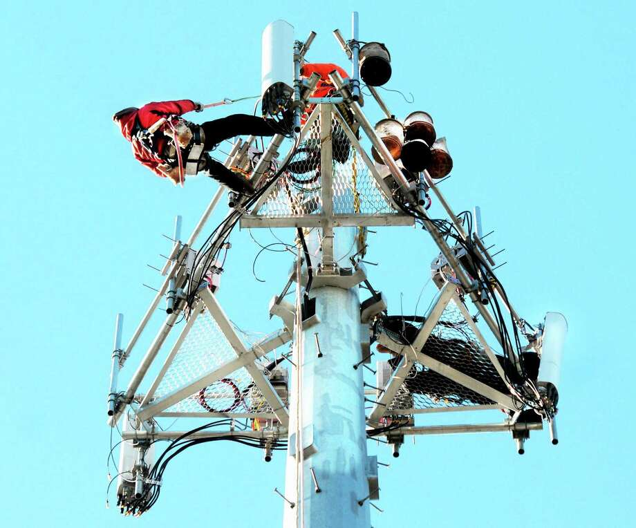 Tower technicians with Anthony's Building Company upgrade a Sprint 4G cell tower in Guilford in this January 2013 file photo. Photo: New Haven Register File Photo  / Mara Lavitt