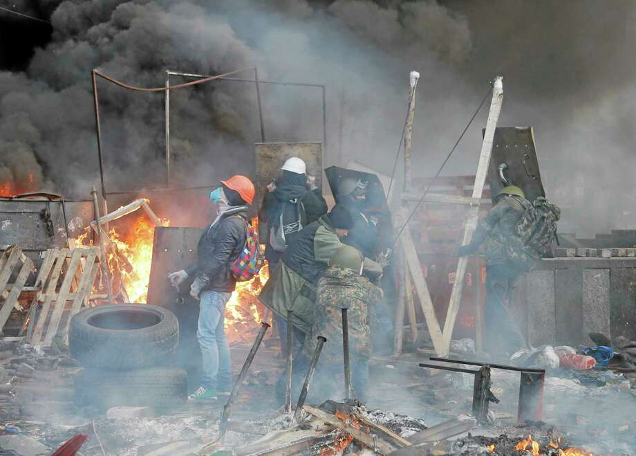 Anti-government protesters use a catapult during clashes with riot police in Kiev's Independence Square, the epicenter of the country's current unrest, Kiev, Ukraine, Wednesday, Feb. 19, 2014. The deadly clashes in Ukraineís capital have drawn sharp reactions from Washington, generated talk of possible European Union sanctions and led to a Kremlin statement blaming Europe and the West. Photo: Efrem Lukatsky — The Associated Press  / AP
