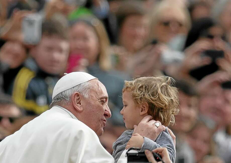 Pope Francis kisse a child as as he tours St. Peter's Square at the Vatican, upon his arrival for a general audience, Wednesday, Feb. 19, 2014. (AP Photo/Alessandra Tarantino) Photo: AP / AP