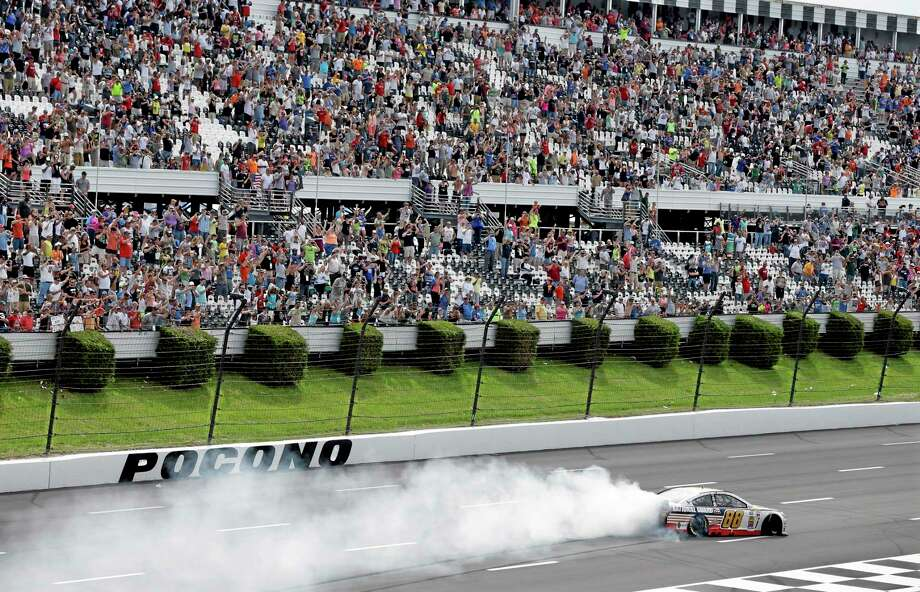 Dale Earnhardt Jr. does a burnout in front fans after winning the Pocono 400 Sunday in Long Pond, Pa. Photo: Mel Evans — The Associated Press  / AP