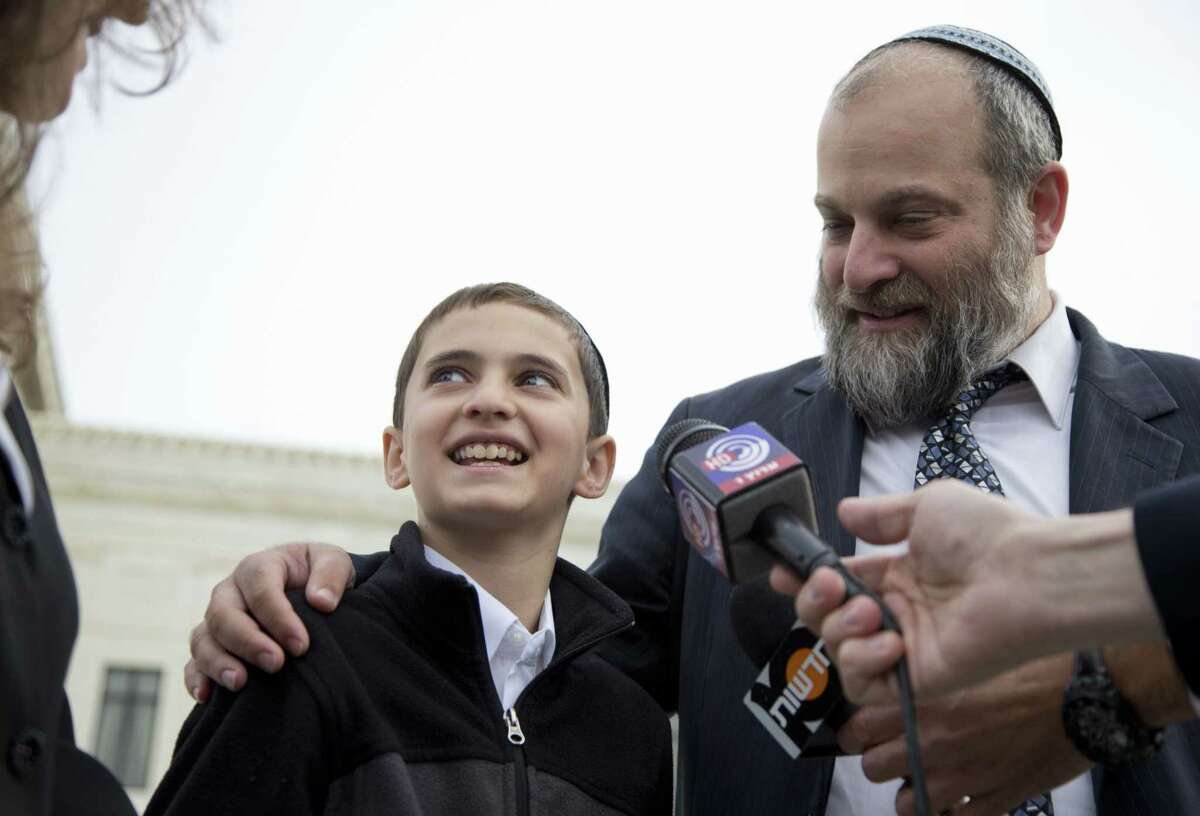 In this Nov. 3, 2014 photo, Menachem Zivotofsky and his father Ari Zivotofsky speaks to media outside the Supreme Court in Washington. The Supreme Court has struck down a disputed law that would have allowed Americans born in Jerusalem to list their birthplace as Israel on their U.S. passports.