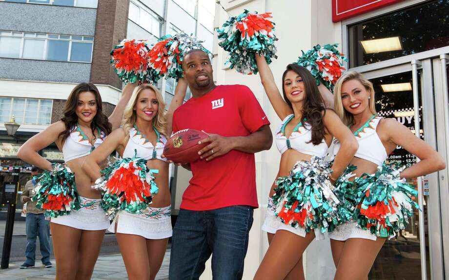 Former NFL star Osi Umenyiora, center, and Miami Dolphins Cheerleaders pose for photographers in central London on Friday. Photo: The Associated Press  / Invision