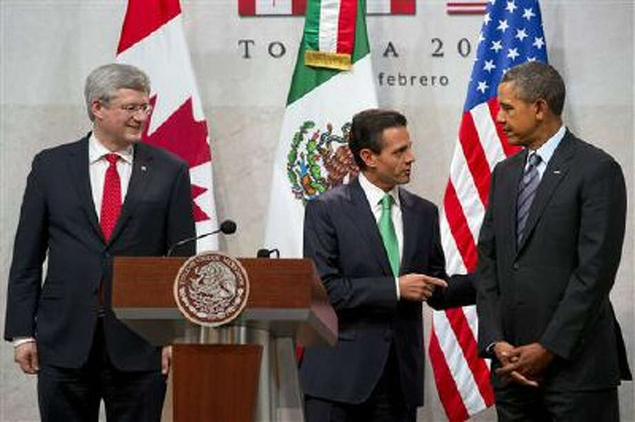 "Canadian Prime Minister Stephen Harper, left, watches as Mexican President Enrique Peña Nieto speaks to U.S. President Barack Obama, before they speak during the seventh trilateral North American Leaders Summit Meeting in Toluca, Mexico Wednesday Feb. 19, 2014. This year's theme is ""North American Competitiveness."" (AP Photo/Jacquelyn Martin) Photo: AP / AP"