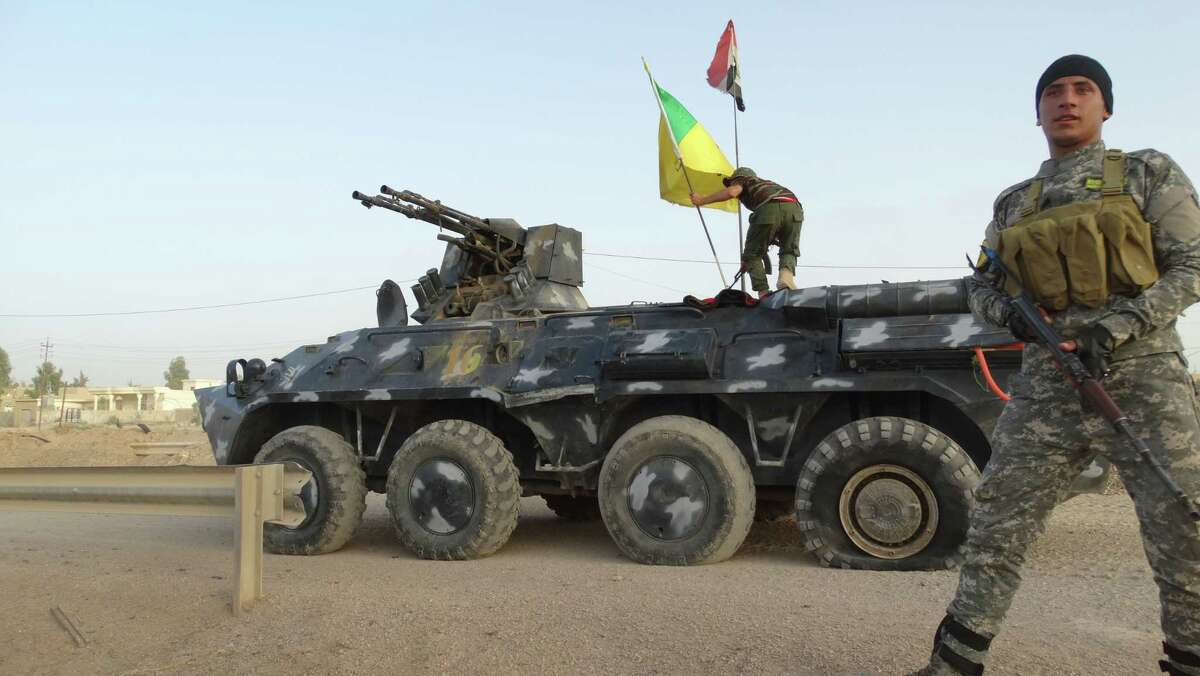 (AP Photo) In this June 4, 2015 photo, Iraqi Federal Police and Shiite Hezbollah Brigade militiamen patrol on the front line in eastern Husaybah, 8 kilometers (5 miles) east of Ramadi, Iraq.