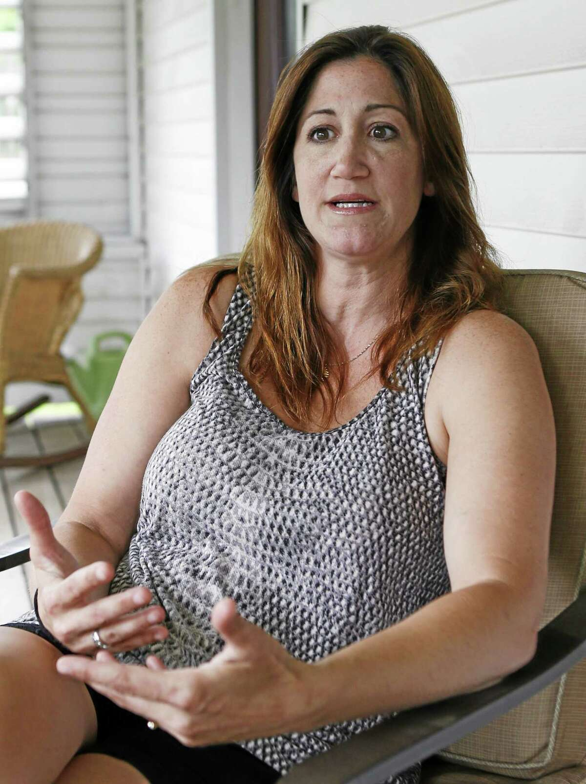 """In this Monday, June 2, 2014, photo, Shannon Spicker, right, sits on her porch in Coraopolis, Pa. and talks about the feelings she had at the time of the O.J. Simpson arrest, trial and decision 20 years-ago. Spicker says """"Most of us didn't understand why it was racially charged."""""""