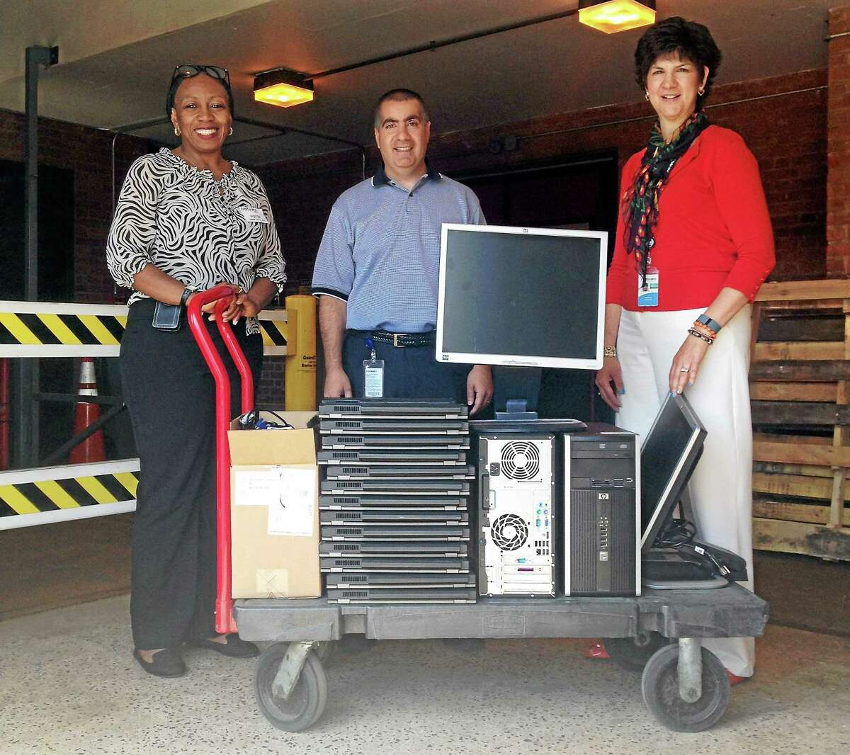 Eversource donated 26 laptops and two desktop computers to the Middlesex Community College Computer Club and Computer Information Technology program. The company's IT manager, Joseph LaBella, and community relations and economic development specialist, Patricia Bandzes, are shown delivering the computers to MxCC Professor Donna Hylton, left.