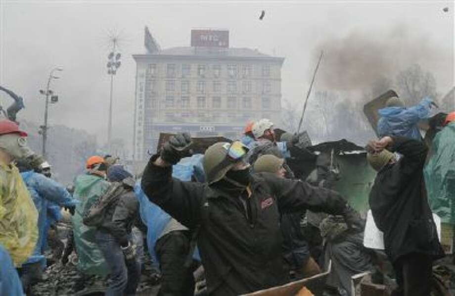 Anti-government protesters throw stones during clashes with riot police in Kiev's Independence Square, the epicenter of the country's current unrest, Kiev, Ukraine, Wednesday, Feb. 19, 2014. The deadly clashes in Ukraine?s capital have drawn sharp reactions from Washington, generated talk of possible European Union sanctions and led to a Kremlin statement blaming Europe and the West. (AP Photo/Efrem Lukatsky) Photo: AP / AP