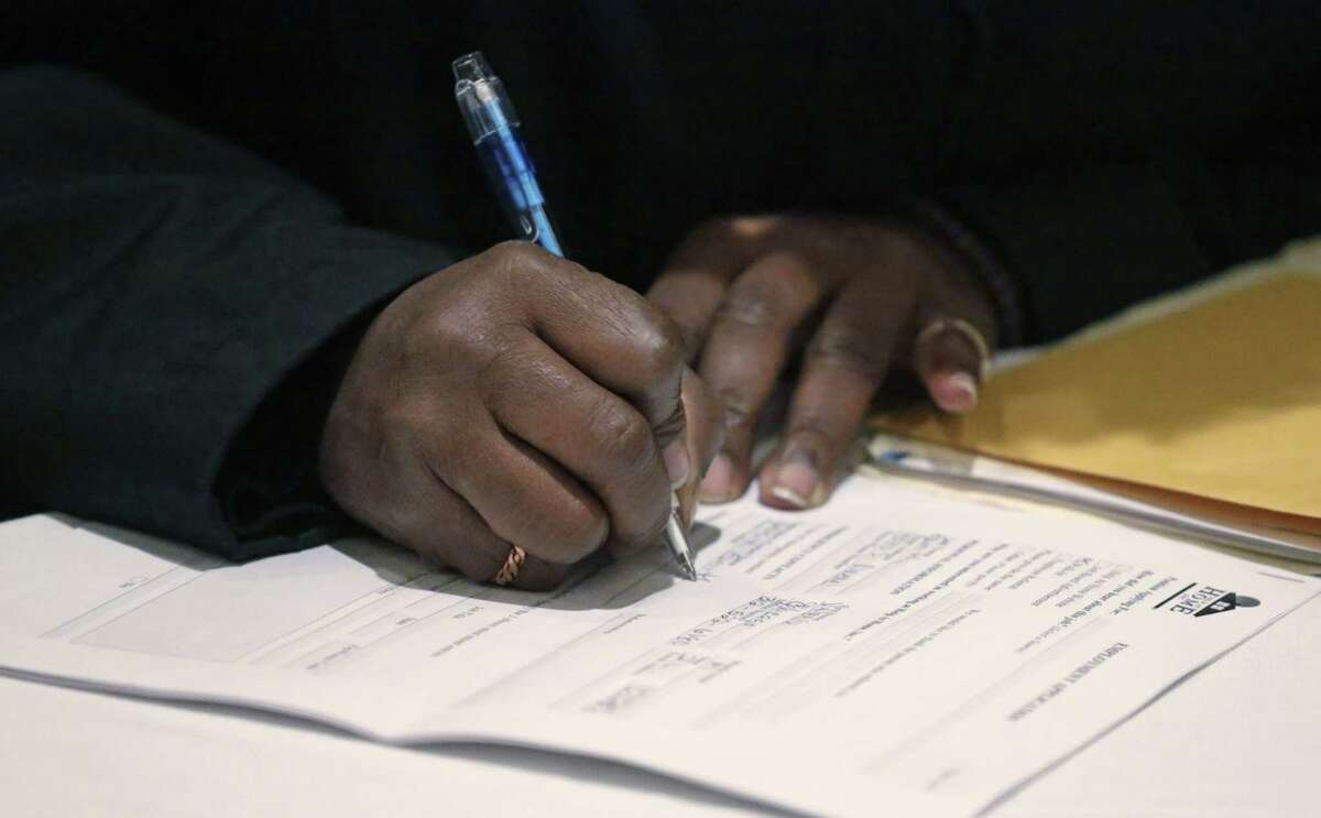FILE - In this April 22, 2015 file photo, a job seeker fills out an application during a National Career Fairs job fair in Chicago. The U.S. Labor Department reports on the number of people who applied for unemployment benefits during the week ending Sept. 19 on Thursday, Sept. 24, 2015.