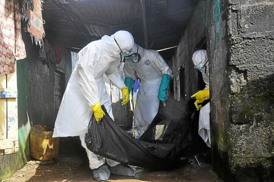 Health workers in protective gear remove the body of a woman suspected to have died from the Ebola virus, near the area of Freeport in Monrovia, Liberia on Oct. 1, 2014. Photo: AP Photo/Abbas Dulleh  / AP