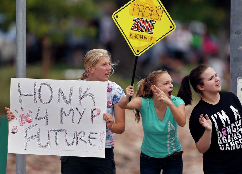 In this Sept. 23, 2014 photo, protesting Pamona High School students, left to right, Ciana Vrtikapa, Tori Suyak, and Becca Ferris engage with passing motorists in a busy intersection near their school, during a multi-school protest against a Jefferson County School Board proposal to emphasize patriotism and downplay civil unrest in the teaching of U.S. history, in Arvada, Colo. (AP Photo/Brennan Linsley) Photo: AP / AP