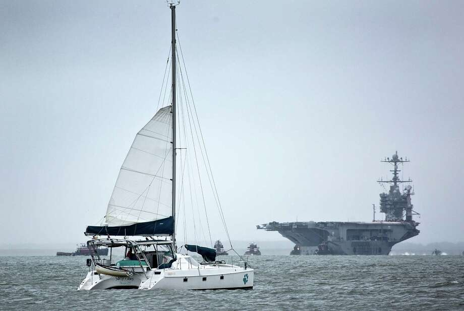 USS Harry S. Truman, CVN-75, returns to Norfolk, ahead of the approach of Hurricane Joaquin as a catamaran sails by in Hampton Va. on Thursday, Oct. 1, 2015. The approach of Hurricane Joaquin, a major Category 3 storm, set to wallop the Bahamas and move toward the U.S. could intensify the damage, but rain is forecast across the region regardless of the storm's path. Photo: Joe Fudge/The Press Via AP   / Daily Press