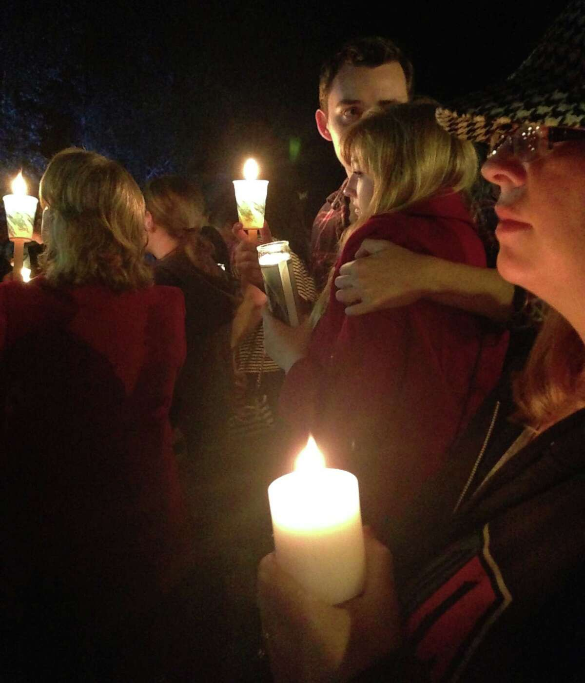 People hold candles Thursday, Oct. 1, 2015, as they attend a memorial for victims of a deadly shooting earlier in the day at Umpqua Community College, in Roseburg, Ore.