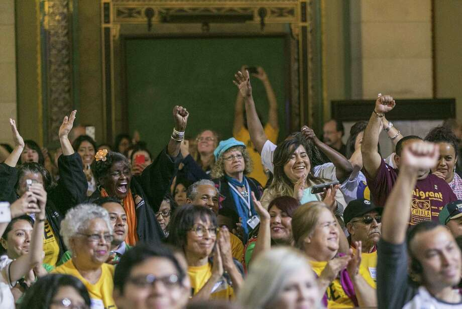 Workers react as the Los Angeles City Council votes 13-1 to raise the minimum wage to $15 an hour by 2020 in Los Angeles Wednesday, June 3, 2015. A final vote will be taken June 10 because the action Wednesday was not unanimous. Photo: AP Photo/Damian Dovarganes  / AP