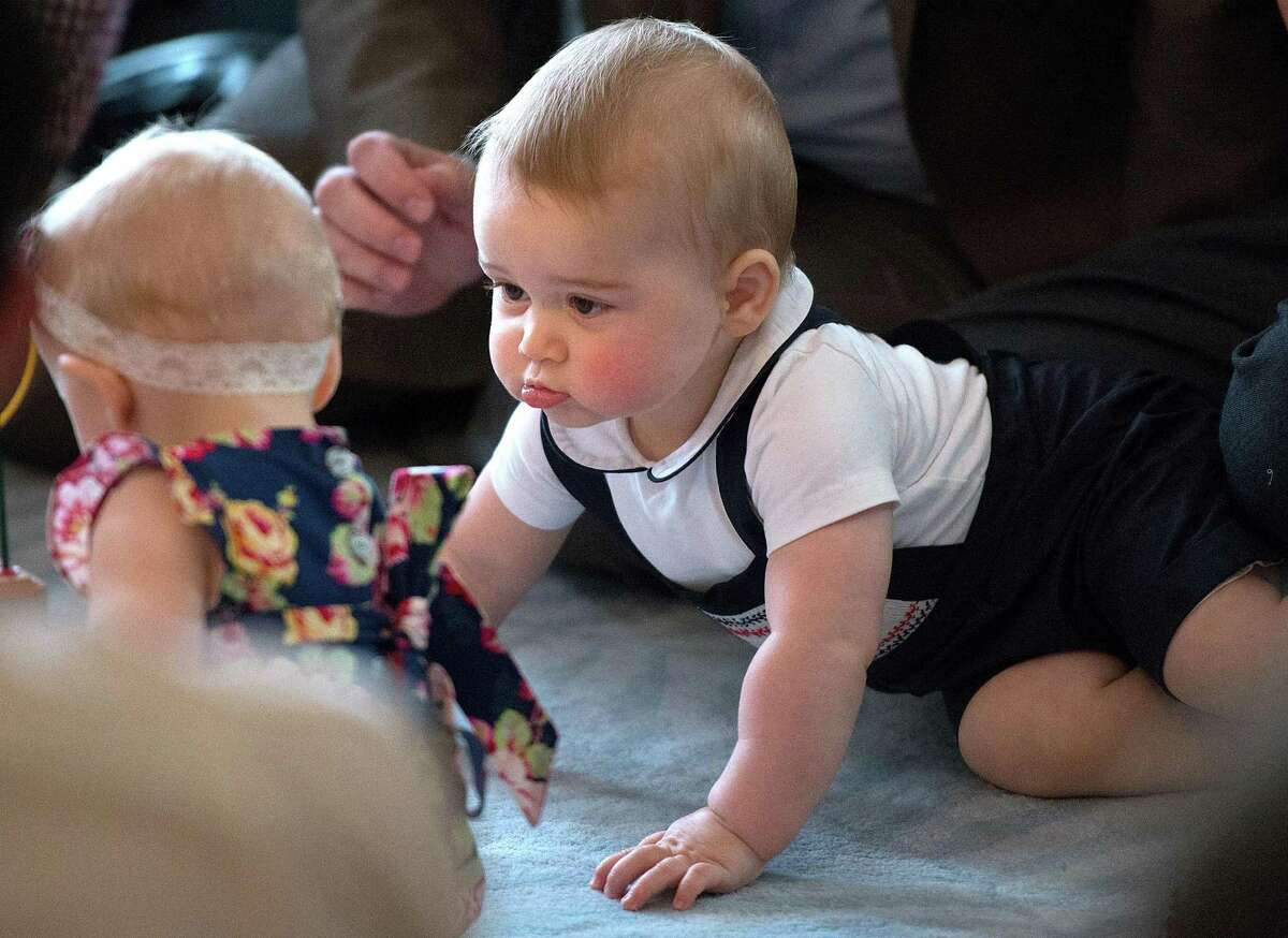 FILE - In this Wednesday, April 9, 2014 file photo, Britain's Prince George, right, plays during a visit to Plunket nurse and parents group at Government House in Wellington, New Zealand. Prince William and his wife Kate are threatening to take legal action against a photographer they say has been monitoring their toddler son Prince George. The palace said Thursday, Oct. 2, 2014 the couple had
