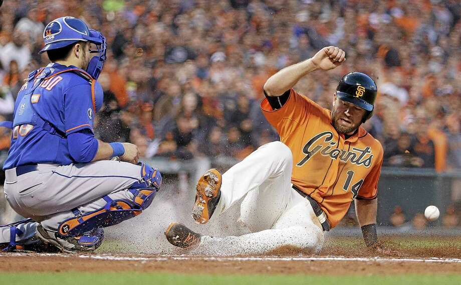 The Giants' Brandon Hicks slides ahead of the throw to score past New York Mets catcher Travis d'Arnaud in the fifth inning of Friday night's game in San Francisco. The Giants won 4-2. Photo: Ben Margot — The Associated Press  / AP