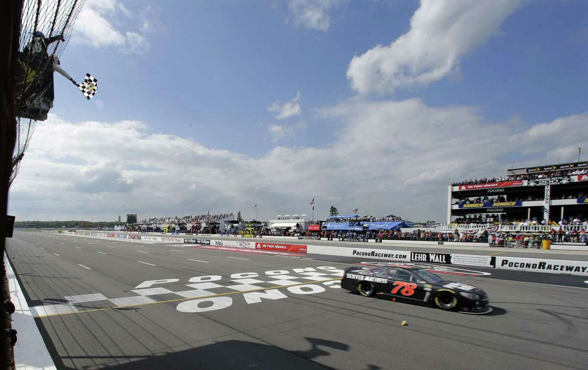 Martin Truex Jr. takes the checkered flag to win at Pocono Raceway in Long Pond, Pa., on Sunday.