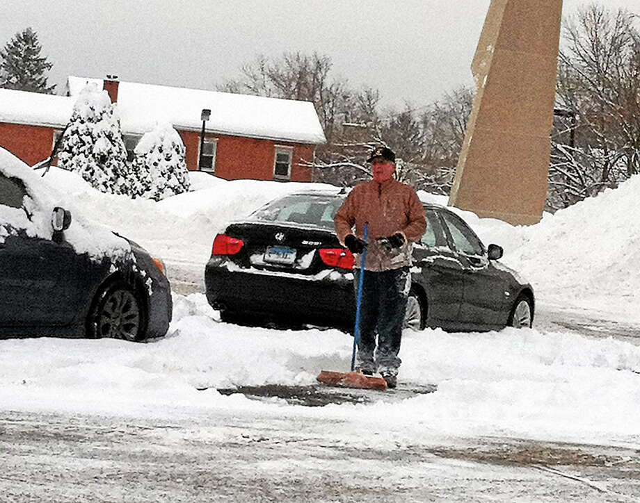Submitted photo. Jack Ostrander, 64, of Middletown, clears snow from the cars of Middlesex Hospital employees as a nice deed for their hard work at the hospital. Photo: Journal Register Co.