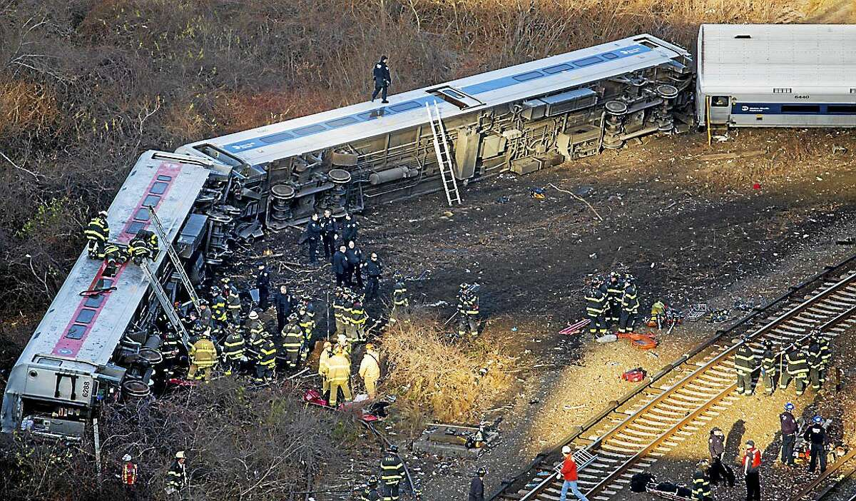 FILE - In this Sunday, Dec. 1, 2013, file photo, first responders work the scene of a derailment of a Metro-North passenger train in the Bronx borough of New York.