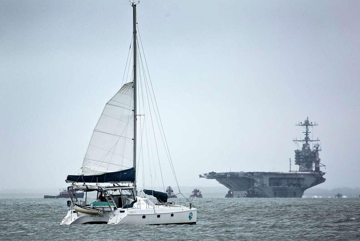 USS Harry S. Truman, CVN-75, returns to Norfolk, ahead of the approach of Hurricane Joaquin as a catamaran sails by in Hampton Va., on Thursday.