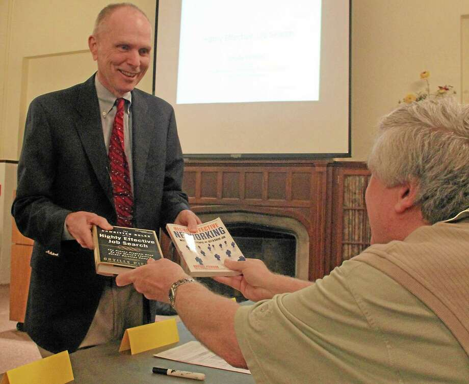 Orville Pierson, author and job search expert, hands his two books to Jeff Grant, a Job and Career Program participant, before starting his workshop at the Russell Library in this file photo Photo: Bob Carlson - Special To The Press