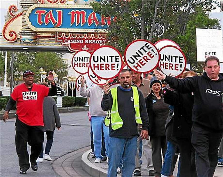 This Oct. 24, 2014 photo shows union members picketing outside the Trump Taj Mahal casino in Atlantic City N.J. On Tuesday Feb. 3, 2015, Local 54 of the Unite-HERE union filed 27 unfair labor practices against Trump Entertainment resorts with the National Labor Relations Board, alleging management threatened workers and unilaterally changed schedules and work rules to hurt workers during a still-unresolved contract dispute. The company declined comment. (AP Photo/Wayne Parry) Photo: AP / AP