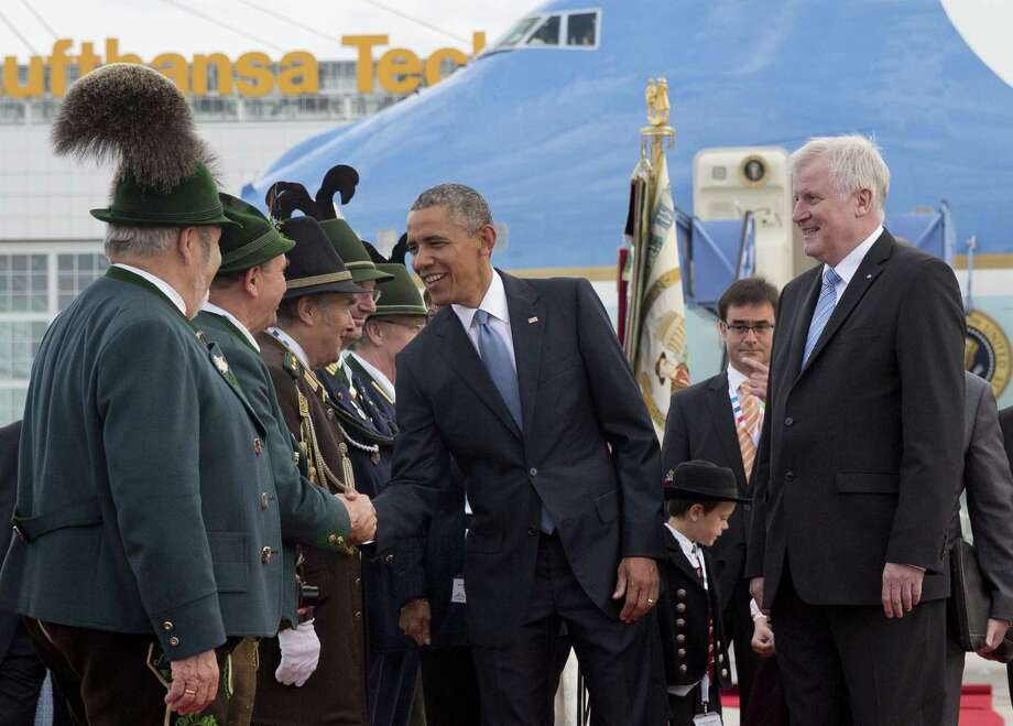 U.S. President Barack Obama, joined by Horst Seehofer, Minister President of Bavaria, right, is greeted by traditionally dressed Bavarian men and women as he arrives on Air Force One at the airport in Munich, Germany on June 7, 2015, en route to the G-7 summit at the Schloss Elmau hotel near Garmisch-Partenkirchen, southern Germany. Photo: AP Photo/Carolyn Kaster  / AP