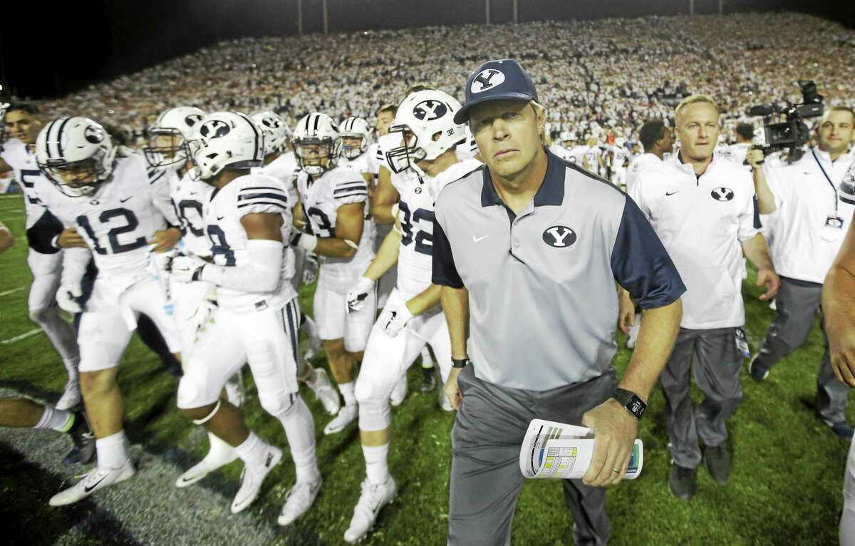 BYU head coach Bronco Mendenhall leads his team on the field earlier this season in Provo, Utah. BYU will host UConn on Friday night.