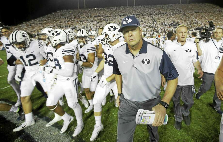 BYU head coach Bronco Mendenhall leads his team on the field earlier this season in Provo, Utah. BYU will host UConn on Friday night. Photo: The Associated Press File Photo  / AP