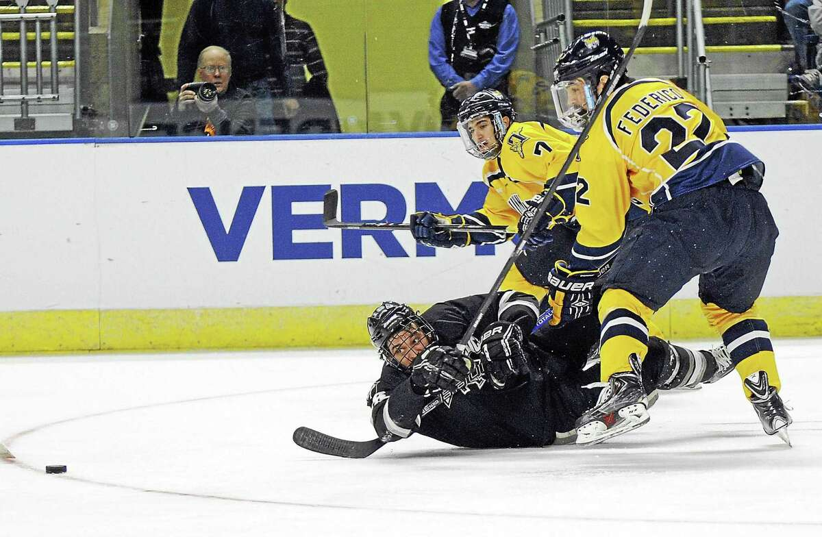 Sam Anas, rear, fights for a loose puck during an NCAA East Regional game against Providence in 2014.