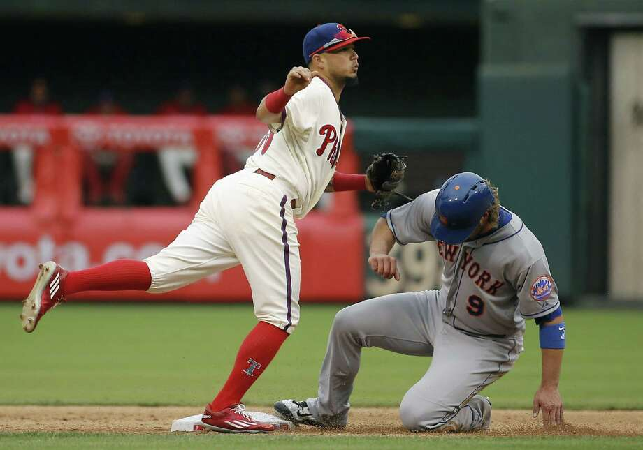 Phillies shortstop Freddy Galvis, left, watches his throw to first base after forcing out the Mets' Kirk Nieuwenhuis at second base on a double play on Thursday. Photo: Matt Slocum — The Associated Press  / AP
